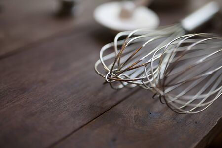 Pastry tools, shallow DOF of wire whisk put on wood table with copy space for bakery background.