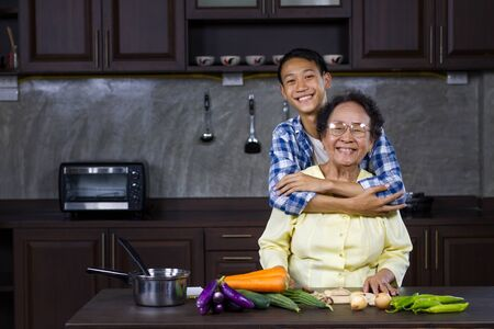 Happy Young Aisan man hugging his grandmother while prepare various of vegetable to cooking at home kitchen. Healthy lifestyle and Domestic life of Asian people concept. Zdjęcie Seryjne - 150545048
