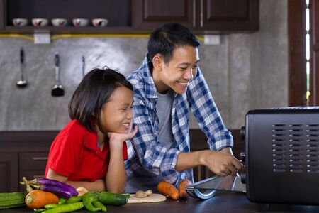 Asian people of Young sister and brother joyful cooking together at home kitchen.