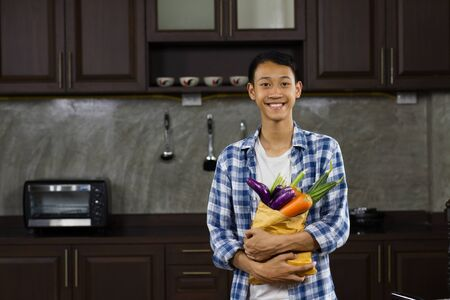 Young asian man hugging some vegetable with smiling and happy face at house kitchen.