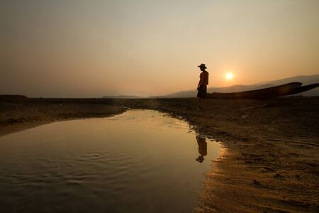 Young man standing near a drying river with a wooden boat at the place that once had been a big lake before, climate change, water crisis concept.