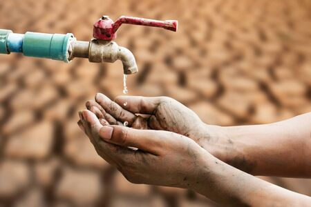 Hand of people wating for a drip of water from a faucet at desert. Climate change, water scarcity and crisis concept. Zdjęcie Seryjne