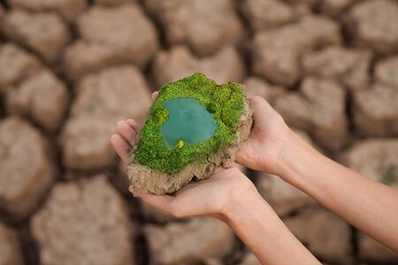 A hand of young man holding a pice of cracked earth thoes have an aboundant of pond of freshwater and green color from plant metaphor Environmental, World water day, water scarcity and climate change.