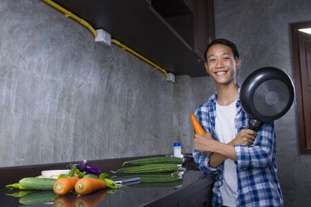 Happy Young asian man holding a frying pan and vegetable with smiling face at kitchen. Asian Domestic life, Self cooking to prevent contagious disease at home concept.