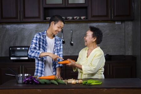 Happy family of young man and grandmother joyful cooking together at home kitchen
