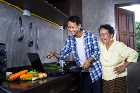 Asian Happy family of young man and grandmother enjoying online food cooking course on laptop together at kitchen. online cooking and healthy lifestyle concept.