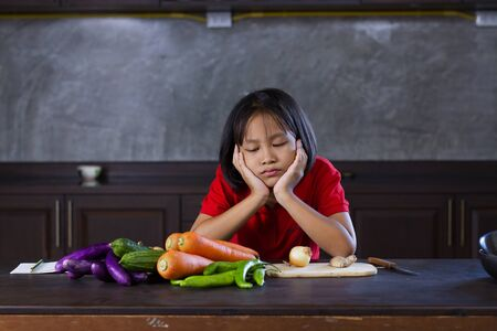 Young asian girl look at vegetable with bored face, Hate vegetable and failue cooking concept. Zdjęcie Seryjne