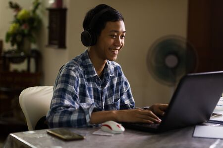 Happy young teenage of Asian boy enjoying with online class chat on laptop camera at home, Night scene.