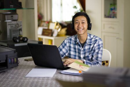 Happy young Asian teenage of a boy wear wireless headset studying online class on laptop computer at home smiling to camera.