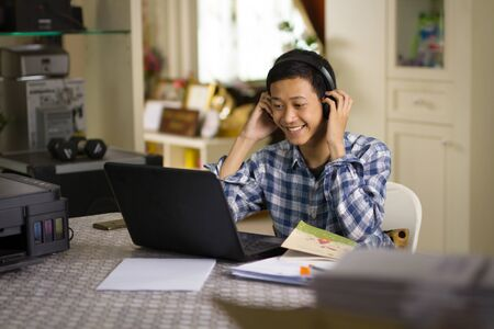 Happy young teenage of Asian boy learning language, look at laptop camera during chat conference with smiling face at home office.