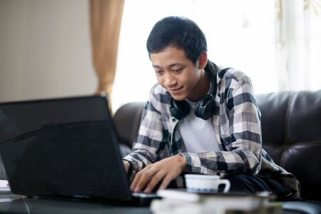 Happy Asia teenager having fun through online class by using a laptop computer at home. e-learning and global education concept. Zdjęcie Seryjne