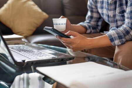 Asian man holding smartphone front of computer laptop while enjoying with a cup of coffee at home office.