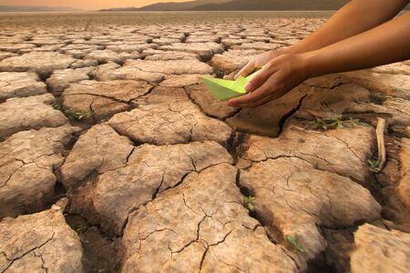 Hand of a man holding a paper boat put on middle dried lake metaphor Water crisis and Climate change concept.