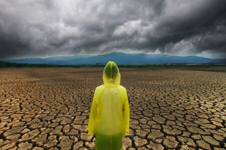 Young man wear a raincoat standing on midle dry lake with storm cloud metaphor climate change and extreme weather on summer