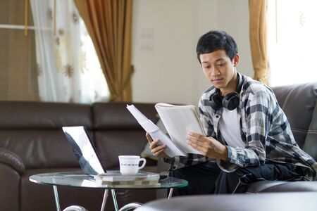 Young asian man looking a work paper or homework while learning online class through laptop computer at home. working from home and online business class.