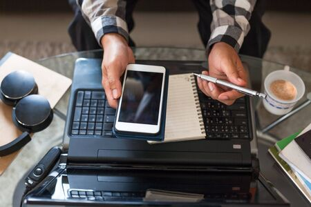 Asian man holding a smartphone and pencil to prepare meeting by using a video conference on laptop at home office. working from home concept. Zdjęcie Seryjne
