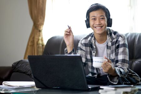 Happy Young asia teenage man wearing a headset, hold a cup of coffee is smiling and having fun with online and business class at home. global education and business, e-learning concept. Zdjęcie Seryjne