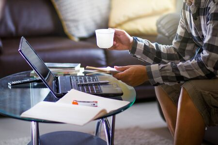 Asian businessman relaxing with a cup of coffee and holding a notebook to prepare work paper at home office.