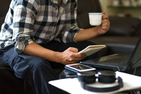 Asian man working from home while enjoy with a cup of coffee and looking to a notbook, prepare to beginning the conference. Home office and online class concept. Zdjęcie Seryjne