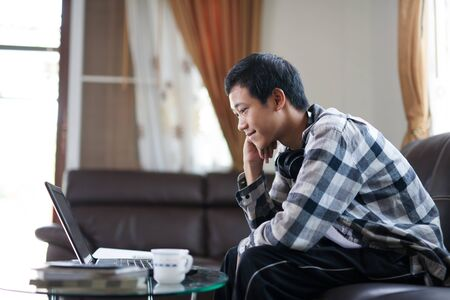 Young asian man smiling and having fun while learning through online class with laptop computer at home, e-learning and education concept. Zdjęcie Seryjne