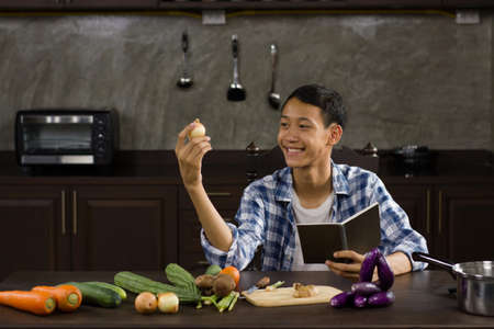 Young asian man teaching a cooking online, talking to a camera while holding some material at home kitchen 免版税图像