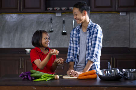 Happy Asian brother and sister have fun while cooking together at home kitchen. Zdjęcie Seryjne