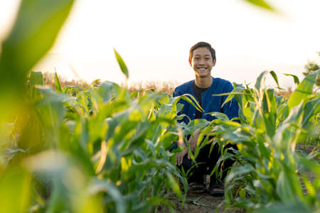 Happy Asian farmer smiling in the corn farm.