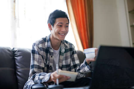 Happy asian man enjoying his online class at home, teaching by a tutor or teacher through laptop computer. Home education concept.