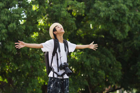 Happy asian man with big backpack of camera gear enjoy in green nature of public park or tropical forest.