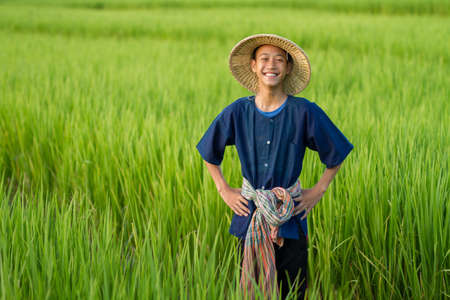 Young asian farmer with hat and tradition costume laughing at green rice fields metaphor happiness and good lifestyle