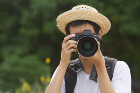 Teen of asian men wearing a hat is holding a camera and taking a photo in green nature background Zdjęcie Seryjne