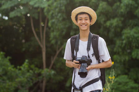 Handsome of Teenage of asian men looking to camera with smiling of hapiness while holding a camera and big backpack in green nature of public park or tropical forest.