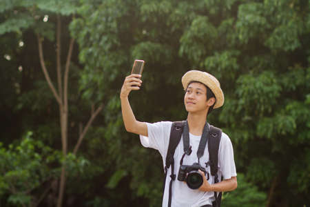 Teen of asian men traveling with big backpack and camera, Taking a photo him self by using a mobile phone in green nature at tropical country or national park. 免版税图像