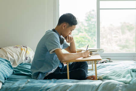 Teenage of young asian boy studying at home