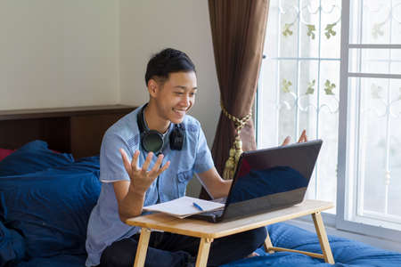 Asian man exciting in front of laptop computer while study at home