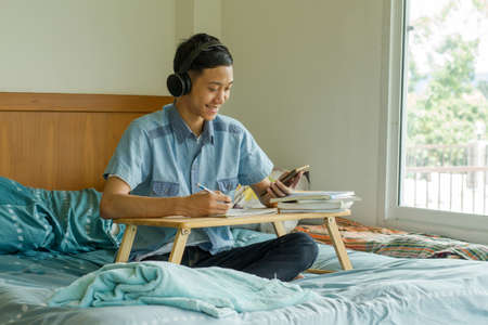 Happy Teenage of Asian boy looking mobile phone and smiling while studying at home. Zdjęcie Seryjne