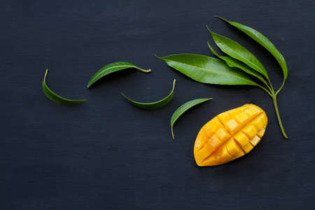 Sliced of ripe mango with tropical leaf flat lay on black wood background