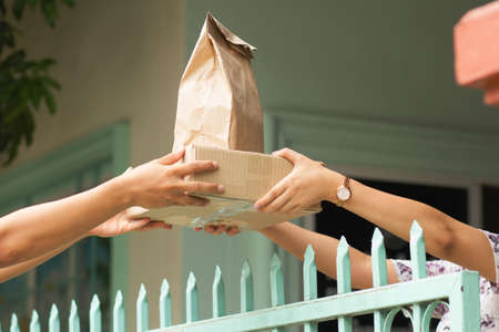 Hand of woman taking a package and food box from delivery man at home