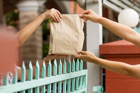Hand of customer or a person taking a package from delivery man at home front