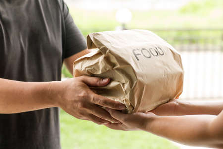 Asian delivery man sending a food box to customer at home