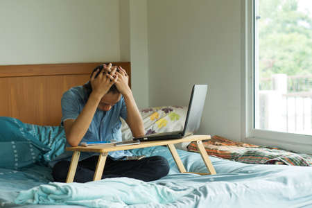 Asian boy get stress and facepalm while studying online through computer laptop at home
