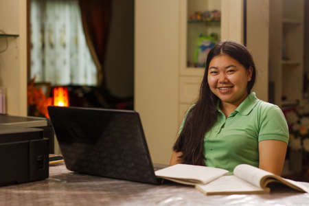 Asian high school girl learning through online class from laptop computer at home while social distancing. 스톡 콘텐츠