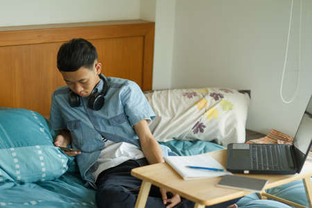 Teenage of asian boy boring to study with himself and playing a mobile phone