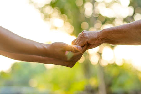 Close up of young man holding hands of senior woman with care. Help family, retirement life and support concept.