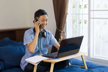 Happy asian boy laughing while using laptop learning online lesson at home during social distancing.