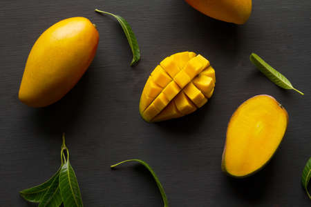Mango tropical fruit in basket on black wood background, top view