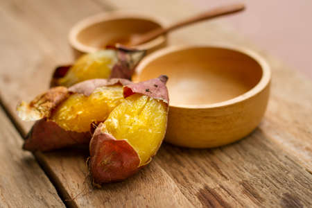 Delicious Baked sweet potato lay on black wood background 스톡 콘텐츠