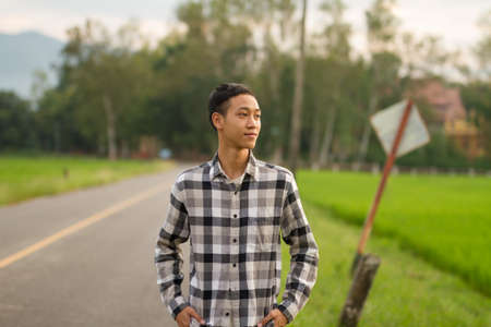 Portrait of young asian boy looking aside to sunlight with rural place on background