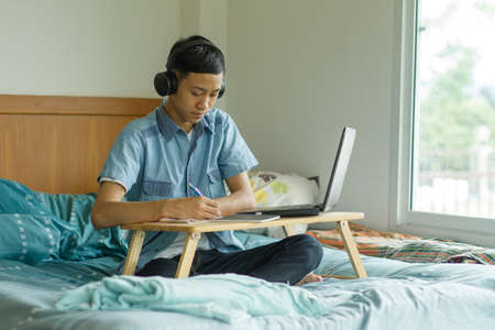 Asian boy study with his online tutor at home. online class and e learning concept.
