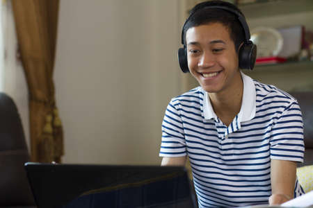 Happy asian boy wear headphone looking to screen of computer laptop and smilling, online course by video call, elearning and online language school at home concept. Zdjęcie Seryjne